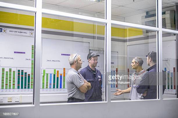 Engineers and workers in discussion in meeting room in car plant