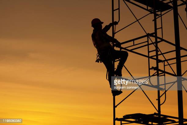 engineers are climbing on the scaffolding in the construction site - twilight stock pictures, royalty-free photos & images
