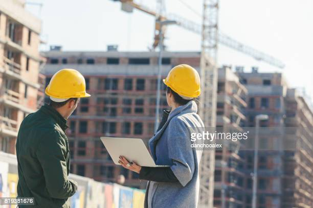 Engineers at construction site planing