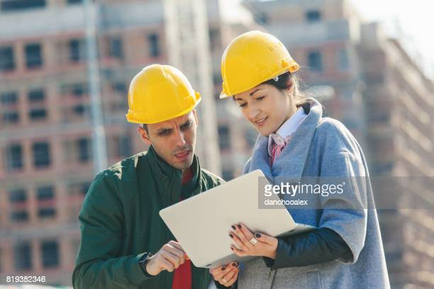 Engineers at construction site using laptop