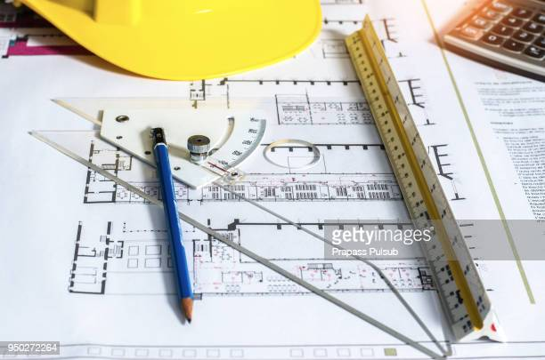 Engineers at work Technical drawing pencils, compasses, calculators and hand. Paper with technical drawings and diagrams.