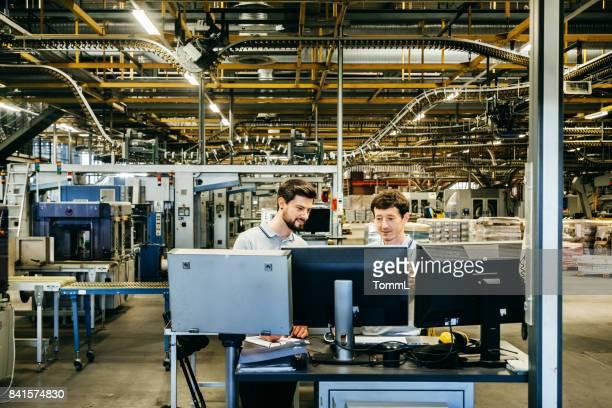 Ingenieure hinter mehreren Computer-Monitoren in einer riesigen Fabrik