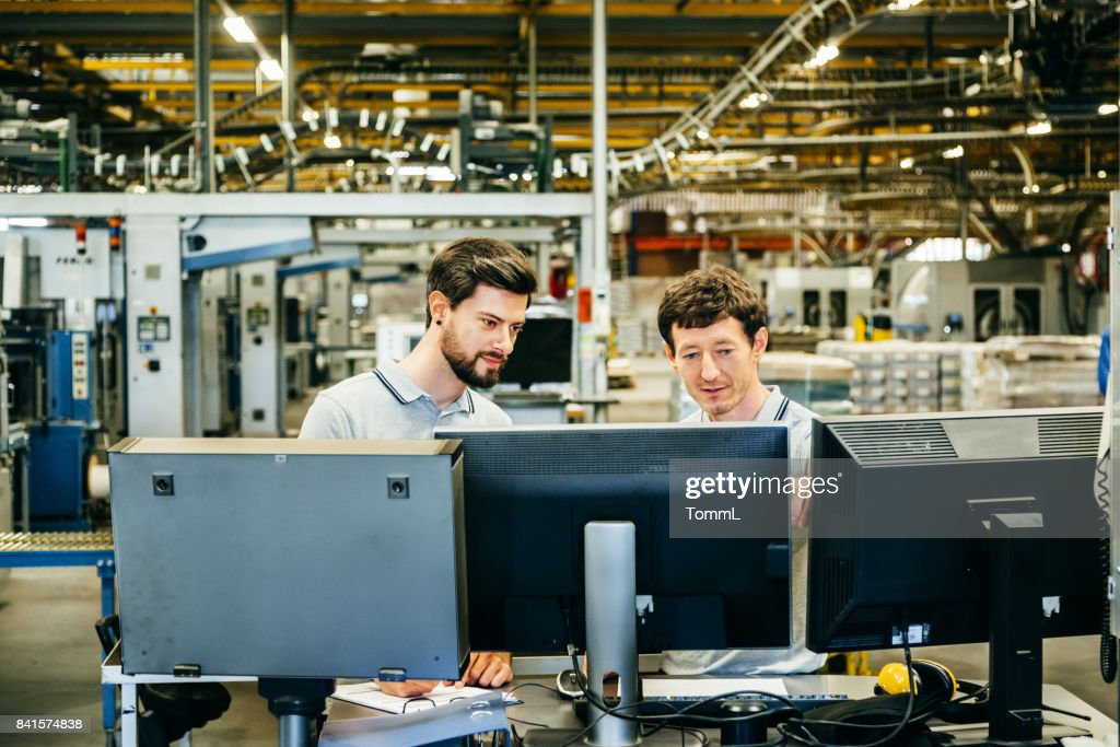 Engineers behind several Computer Monitors in a huge factory : Stock Photo