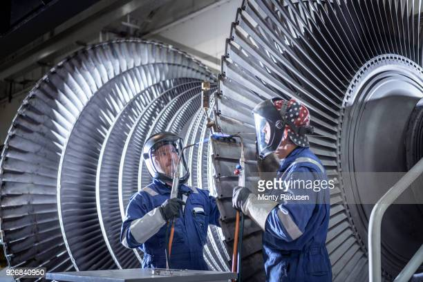 Engineers brazing ends of blades on low pressure steam turbine in turbine maintenance factory