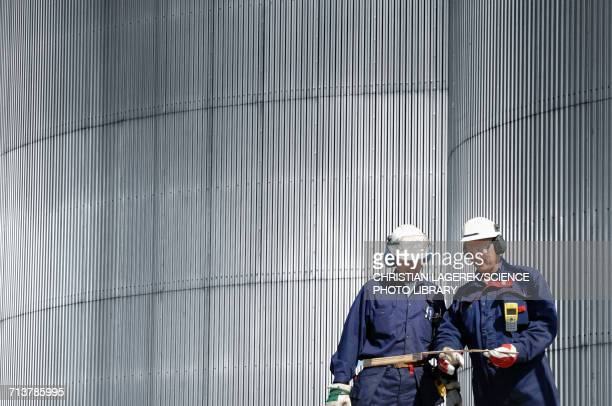 engineers by oil storage tower - refinery stock pictures, royalty-free photos & images