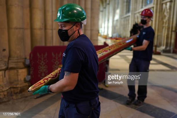 Engineers carry a newly restored organ pipe from the York Minster organ following refurbishment on September 15 2020 in York England The...