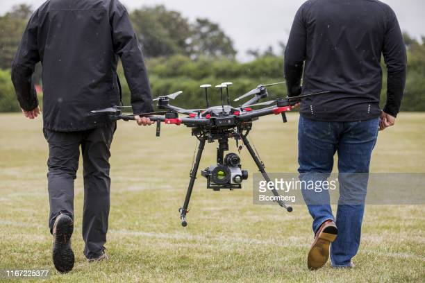 Engineers carry a Precision Hawk drone targeted at onshore maintenance and checking gas leaks at a BP Plc immersive technology event at the company's...