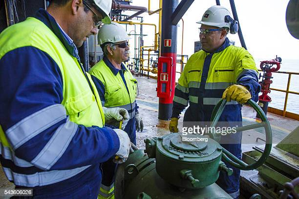 Engineers chat whilst checking pipe valves on the towel deck aboard the Casablanca oil platform operated by Repsol SA in the Mediterranean Sea off...