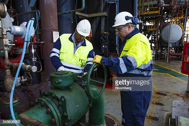 Engineers check pipe valves on the towel deck aboard the Casablanca oil platform operated by Repsol SA in the Mediterranean Sea off the coast of...