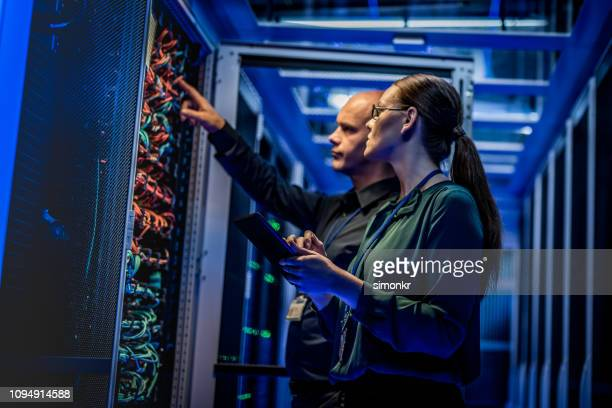 it-ingenieurs controleren van servers in de serverruimte - complex stockfoto's en -beelden