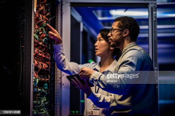 it engineers checking servers in server room - server room stock pictures, royalty-free photos & images