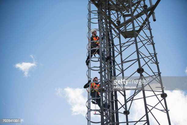 Engineers climbing transmission tower, low angle view