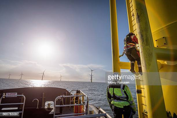 Engineers climbing wind turbine at offshore wind farm