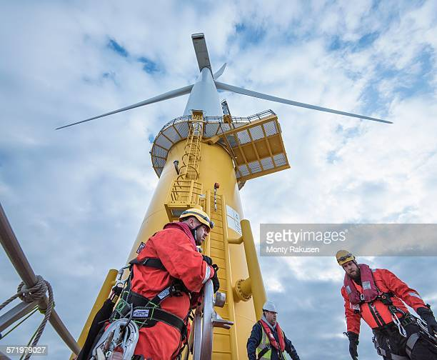 engineers climbing wind turbine from boat at offshore windfarm, low angle view - marine engineering stock pictures, royalty-free photos & images