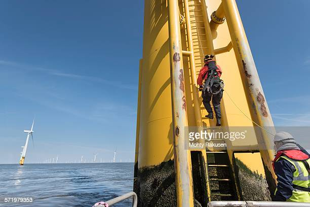 Engineers climbing wind turbine ladder from boat at offshore windfarm