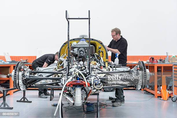 Engineers constructing racing car in racing car factory