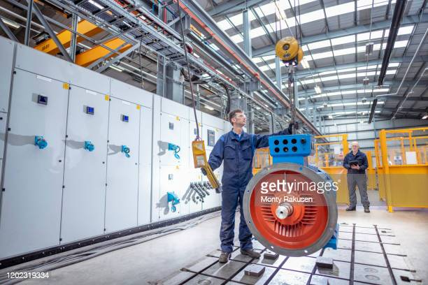 engineers craning generator on to test bed in electrical engineering factory - generator stock pictures, royalty-free photos & images