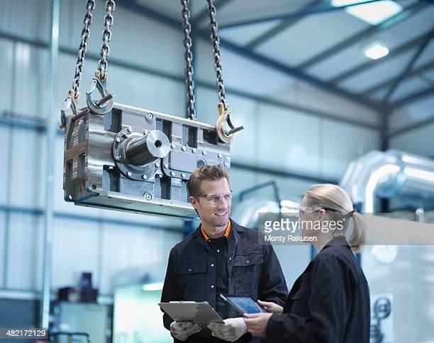Engineers discuss plans on digital tablet in engineering factory
