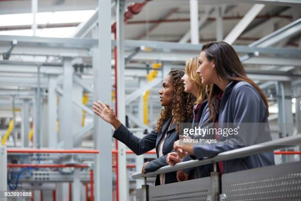 engineers discussing at railing in car plant - leaning stock pictures, royalty-free photos & images