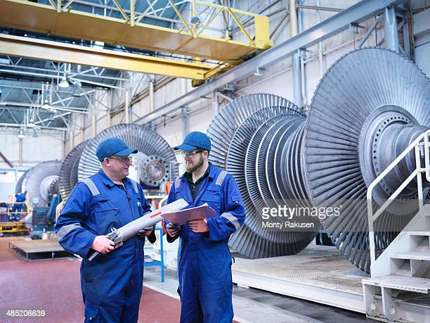 Engineers discussing rotor blade in turbine repair workshop