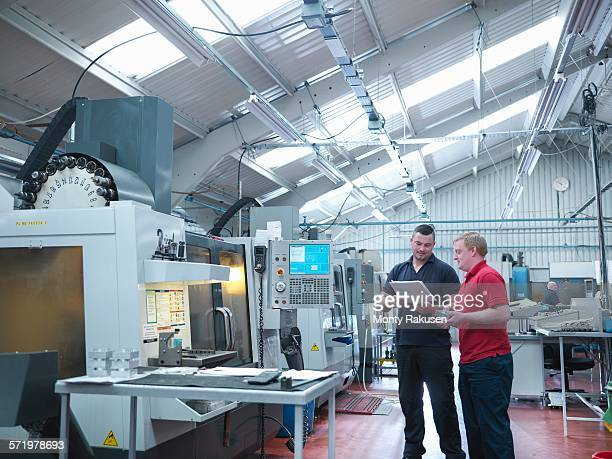 Engineers discussing work in front of CNC machines in engineering factory