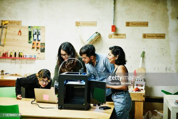 engineers examining plans on laptop while prototyping parts for project on 3d printer in workshop - premium access stock pictures, royalty-free photos & images