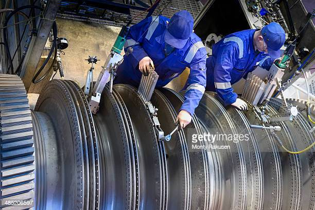 Engineers fitting blades to steam turbine in turbine repair bay