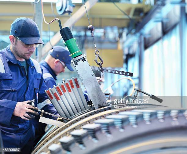 Engineers fitting blades to steam turbine in turbine repair works