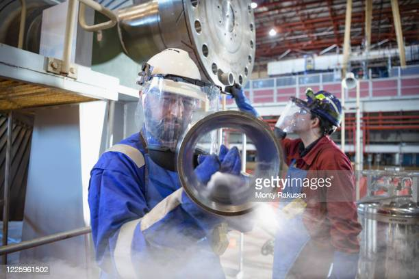 engineers fitting parts in a  power station with liquid nitrogen. - atomic imagery stock pictures, royalty-free photos & images