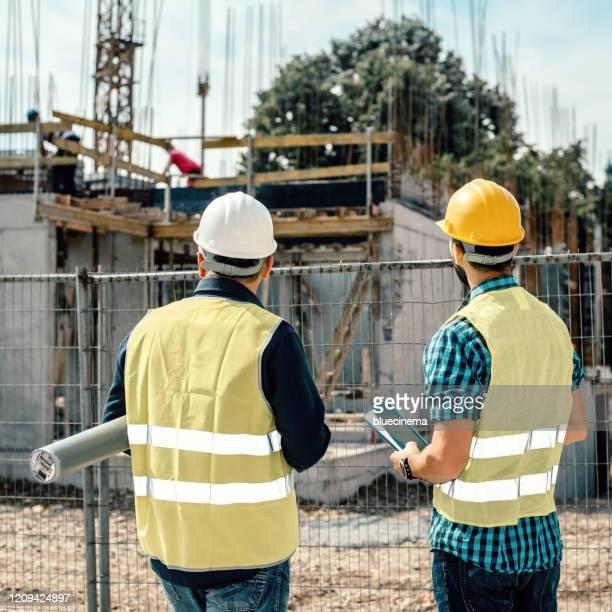 engineers having meeting regarding new construction phase - estrutura construída imagens e fotografias de stock