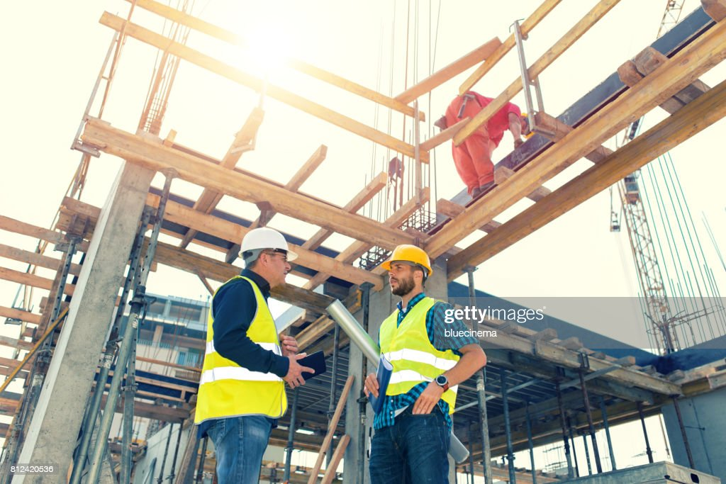 Engineers having meeting regarding new construction phase : Stock Photo