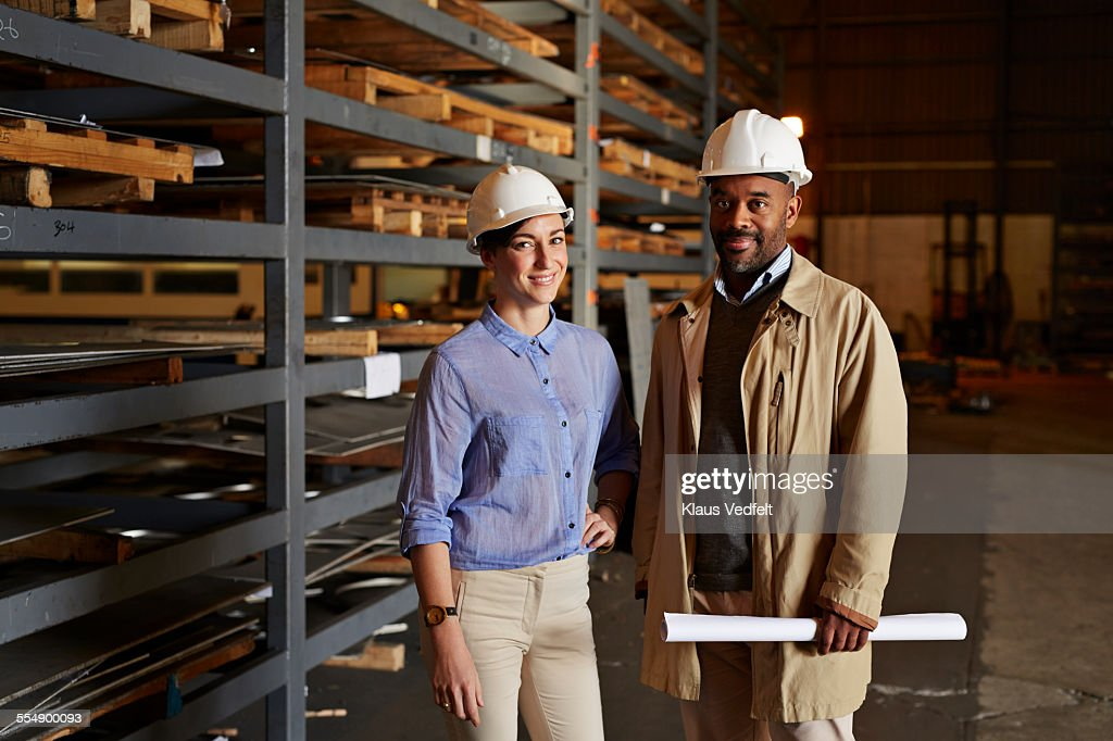 Engineers holding blueprints at factory : Stock Photo