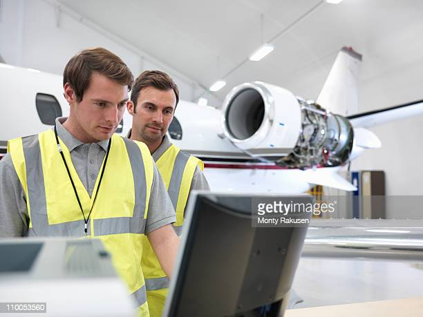 Engineers in aircraft hangar with jet