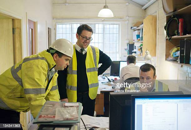 engineers in discussion around computer - newpremiumuk stock pictures, royalty-free photos & images