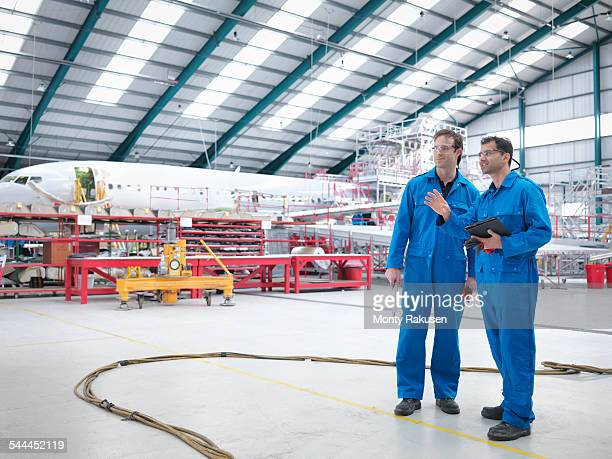 engineers in discussion in aircraft maintenance factory - ジャンプスーツ ストックフォトと画像