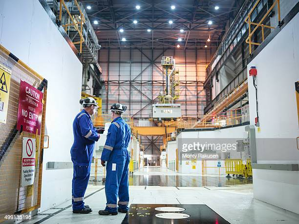 engineers in discussion in reactor hall in nuclear power station - nuclear reactor stock pictures, royalty-free photos & images