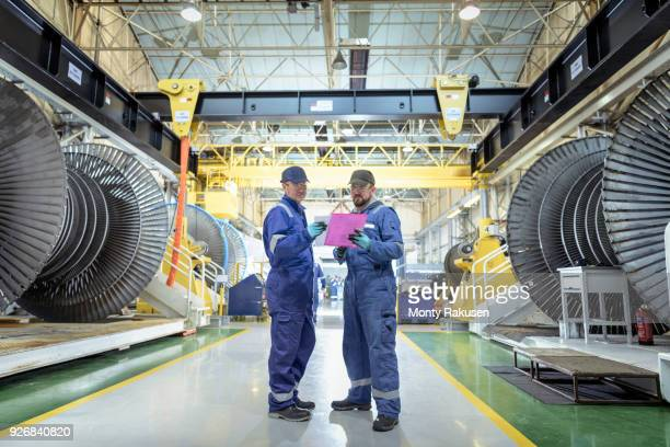 Engineers in discussion in turbine maintenance factory
