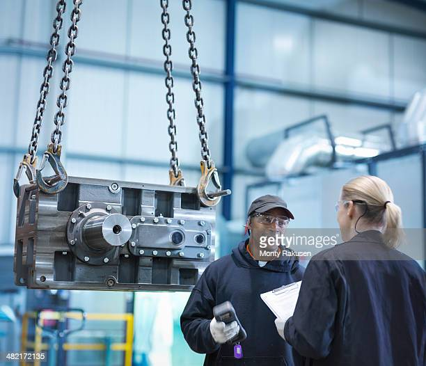 Engineers in discussion next to industrial gearbox in engineering factory