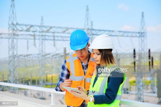 engineers in front of power station - power line stock pictures, royalty-free photos & images