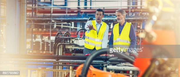 Engineers in reflective vests examining machinery