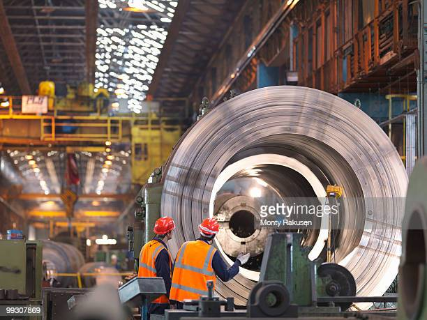 Engineers In Steel Factory With Lathe