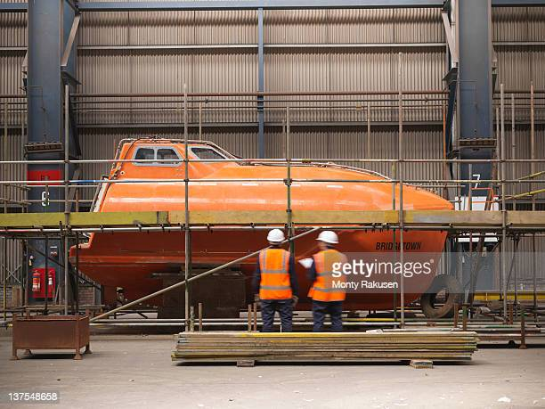 Engineers inspect lifeboat in shipping yard