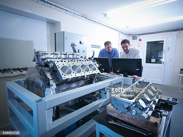 engineers inspecting automotive engine in test facility - engine stock pictures, royalty-free photos & images