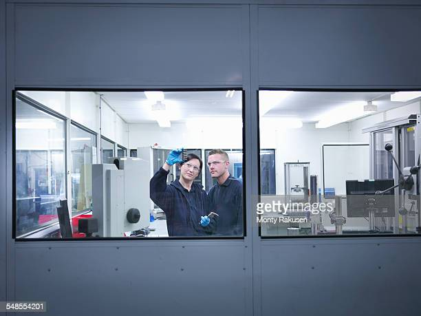 Engineers inspecting automotive parts in clean room of factory