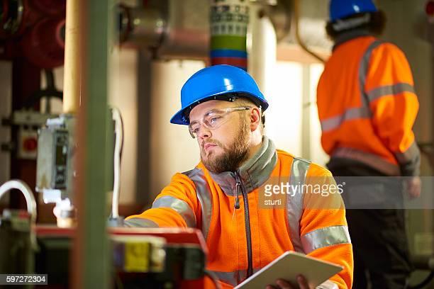 Engineer's inspecting boiler room machinery