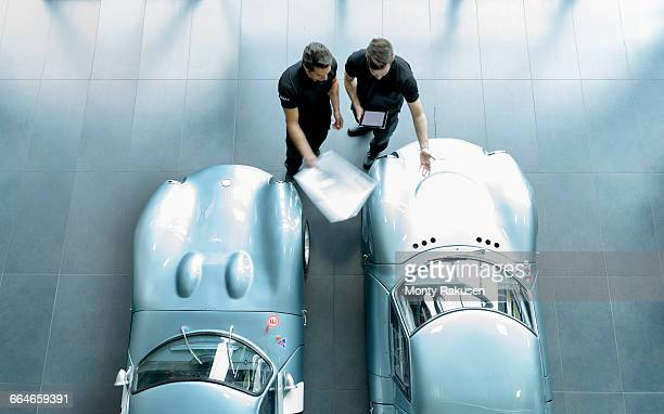 engineers inspecting classic racing cars in racing car factory, overhead view - vintage auto repair stock pictures, royalty-free photos & images