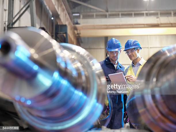 Engineers inspecting finished steel rollers in engineering factory