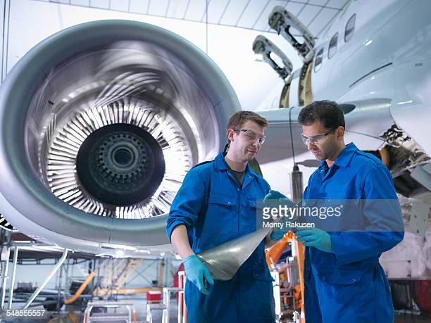 Engineers inspecting jet engine turbine blade in aircraft maintenance factory