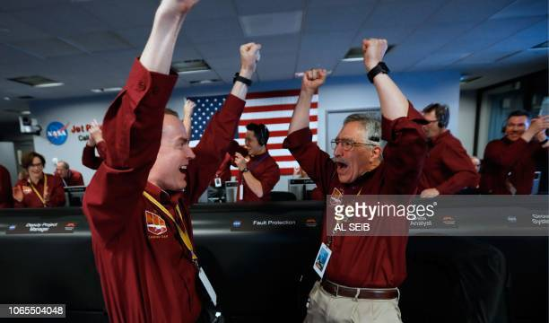NASA engineers Kris Bruvold and Sandy Krasner react after the successful landing by the InSight spacecraft on the planet Mars from the Mission...