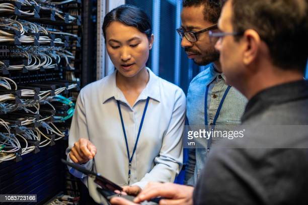IT engineers looking at a digital tablet next to a server